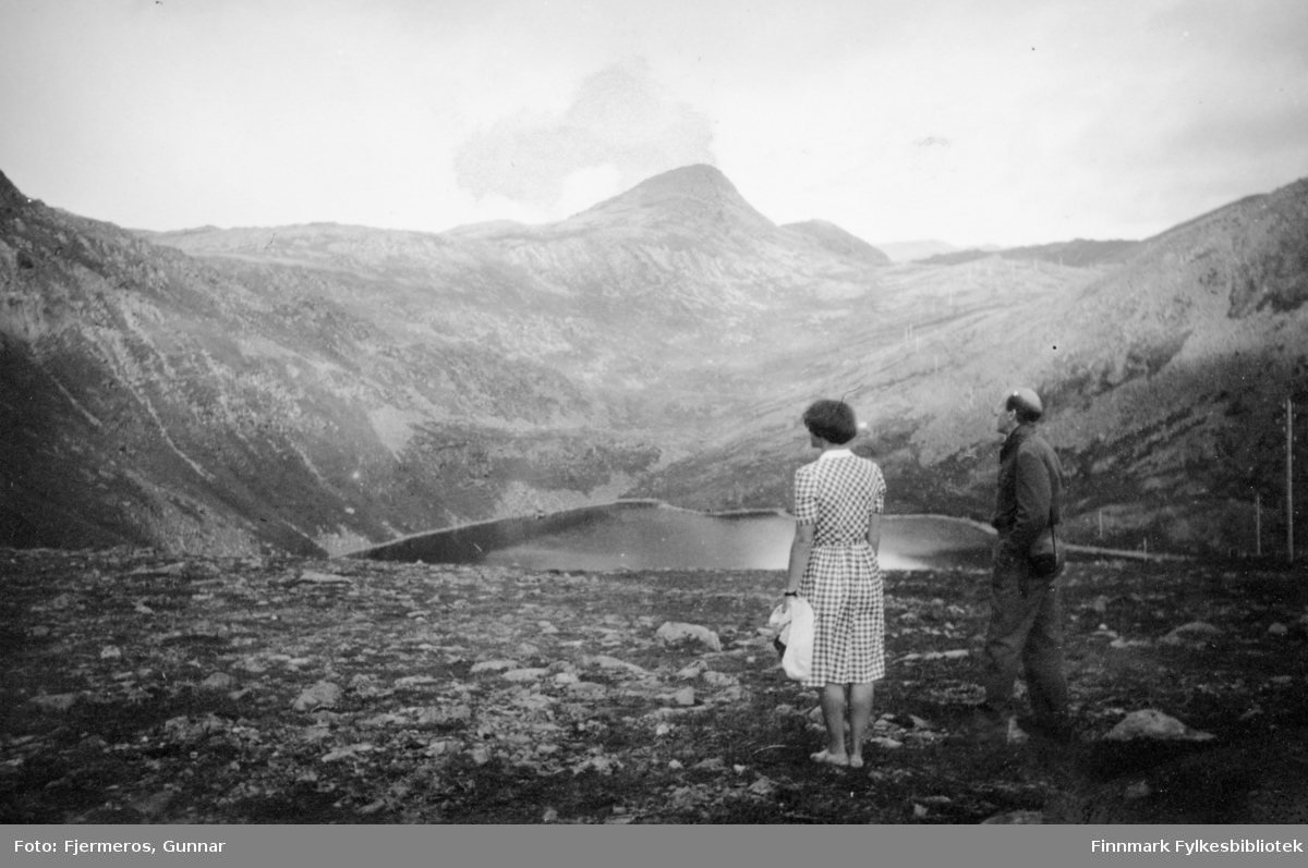 To personer ved et fjellvann i nærheten av Honningsvåg sommeren 1946. Helt øverst på bildet ses en liten prikk som er en Fjellvåk. Personer er ukjente.