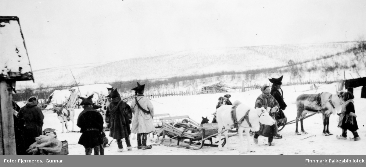 Flere personer i sameklær står rundt på området med tre rein og sleder rundt seg. Stedet er ukjent, men kan være i nærheten av Jergul i påsken 1947.