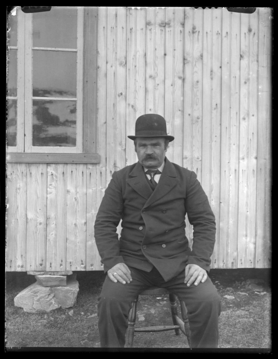 En mann, Hans Aleksandersen, sitter på en krakk ved en husvegg i Makkaur. Mannen er kledd i en mørk dress med slips og knall. Han har giftering og bart. På veggen til venstre vises en del av et vinduskarm.