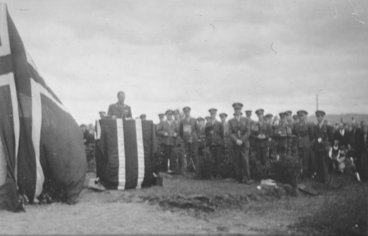 Generalmajor A. D. Dahl taler under avdukingseremoni av bauta til minne for de falne i Alta bataljon under krigen. Statuen ble avduket 24.7.1949.  Til høyre kan man se divisjonsmusikken.