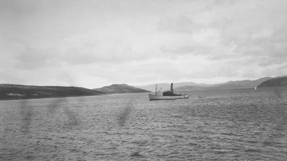 Bøkfjorden. En båt ligger ute på havet. I bakgrunnen kan man se fjell.