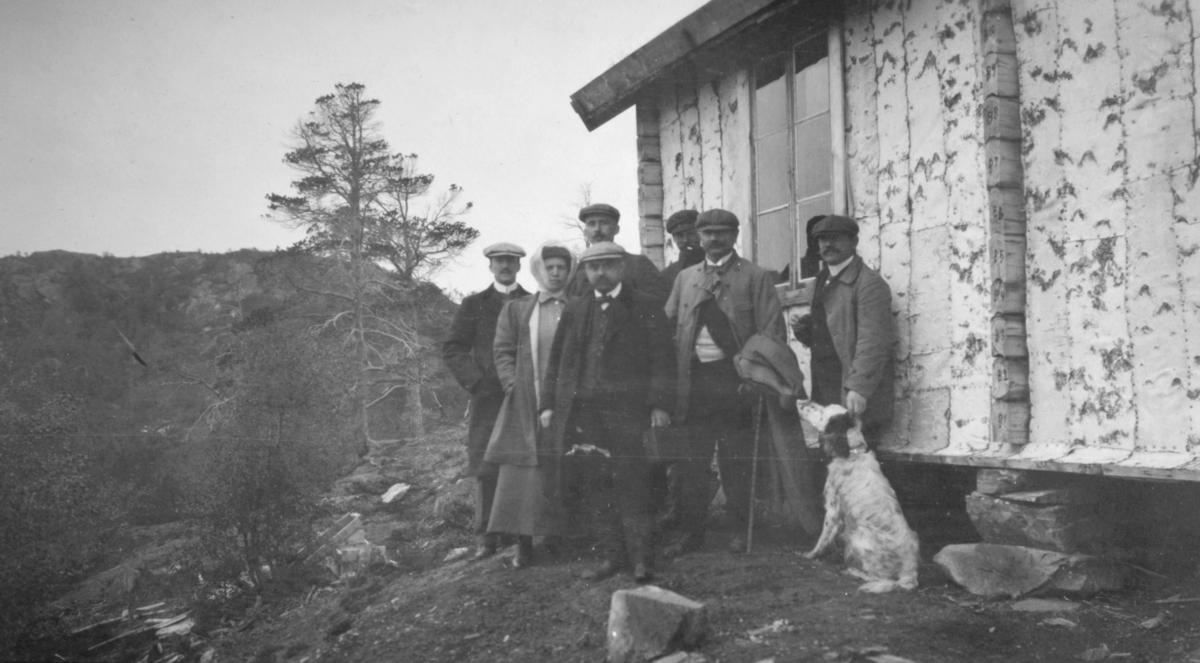 Gruppeportrett ved en hyttevegg, muligens i gruveområdet. Wiull foran i bildet, damen bak ham kan være Helga Wiull.