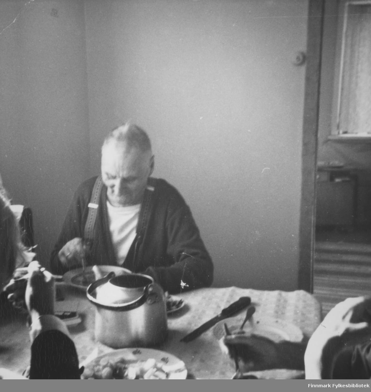 Viktor Karakka sitter ved kjøkkenbordet i Skallelv. På bildet vises såvidt to andre, ukjente, personer.