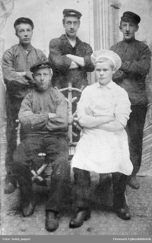 Gruppebilde av fem unge menn tatt hos fotografen Soini i Vadsø. Georg Bjerk og Edvard Pettersen sittende foran, den sistnevnte kledd som kokk, og J.Korbi, Eivind Riise og A.Hågensen stående bak dem. Bildet er tatt ca. 1905-1910.