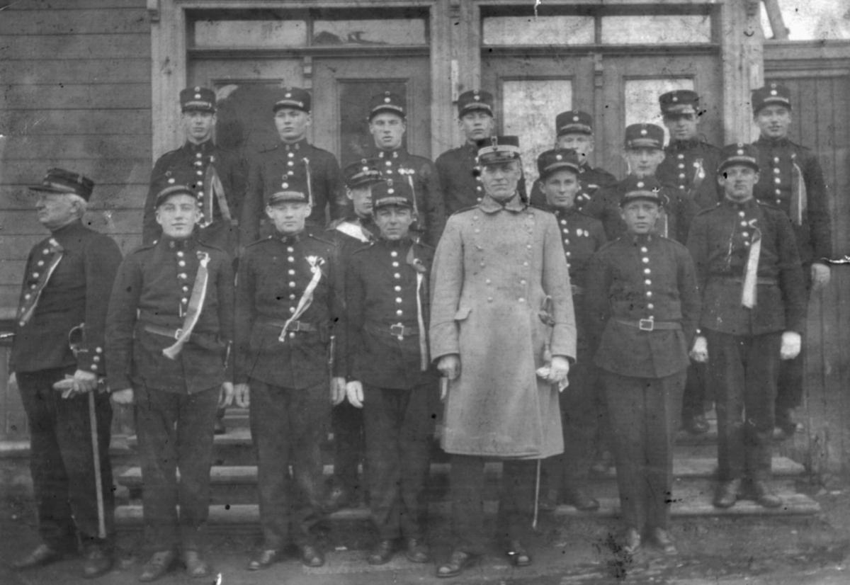 """""""Fra Korporalskolen i Vadsø. De øvrige elever ved Korp.skolen."""" Mannen i midten med lys frakk er Kaptein Løken, sjef av skolen. Mannen helt til venstre i forgrunnen er Ernst J.Lebesby."""