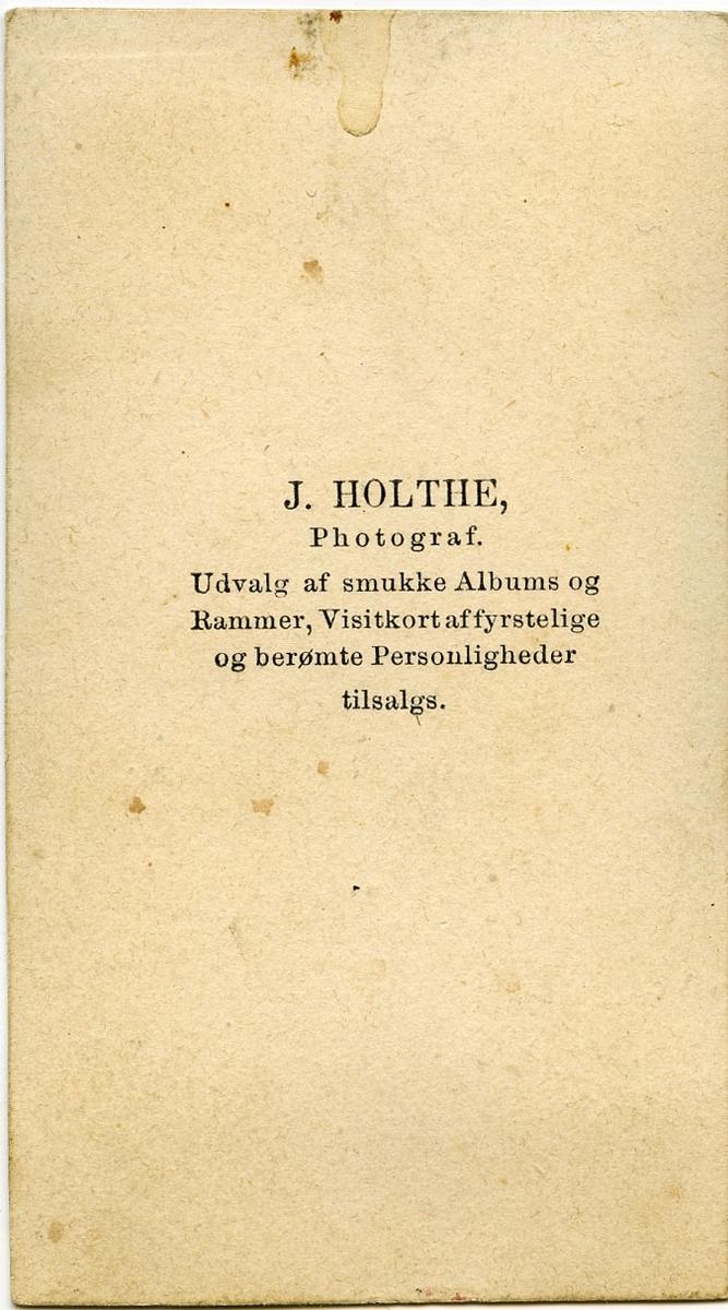 """Ukjent mann.  Påskrift bak bilde: """"J. Holthe. Photograf. Udvalf af smukke Albums og Rammer, Visitkort affyrstelige og berømte Personligheter tilsalgs""""."""