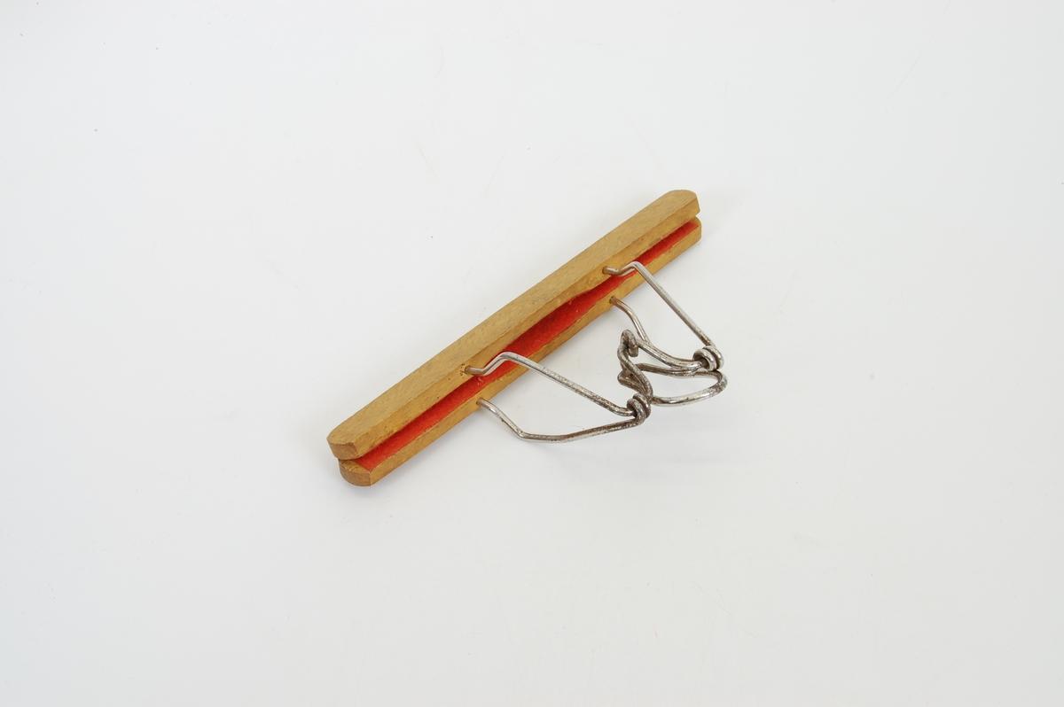 Form: to avlange trestykker som holdes sammen med en klemmeanordning og låses ved at metallkroken klemmes på plass.