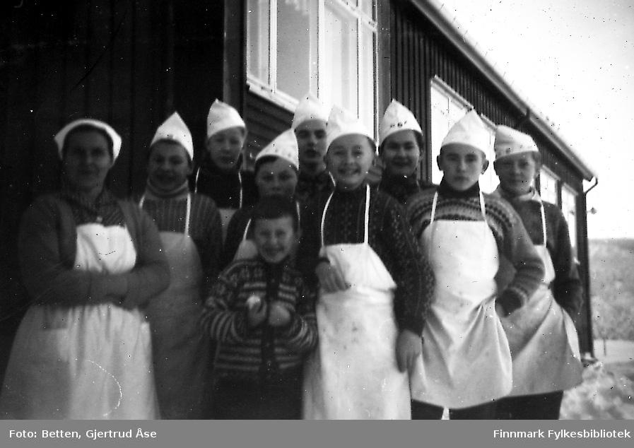 Gutter fra framhaldsskolen på kjøkkenopplæring i Seida skole og internat. Ni gutter kledd i hvite forklær og luer står ute ved skolekjøkkenet. En kvinnelig lærer står ved siden av dem. Bildet er litt uskarpt.