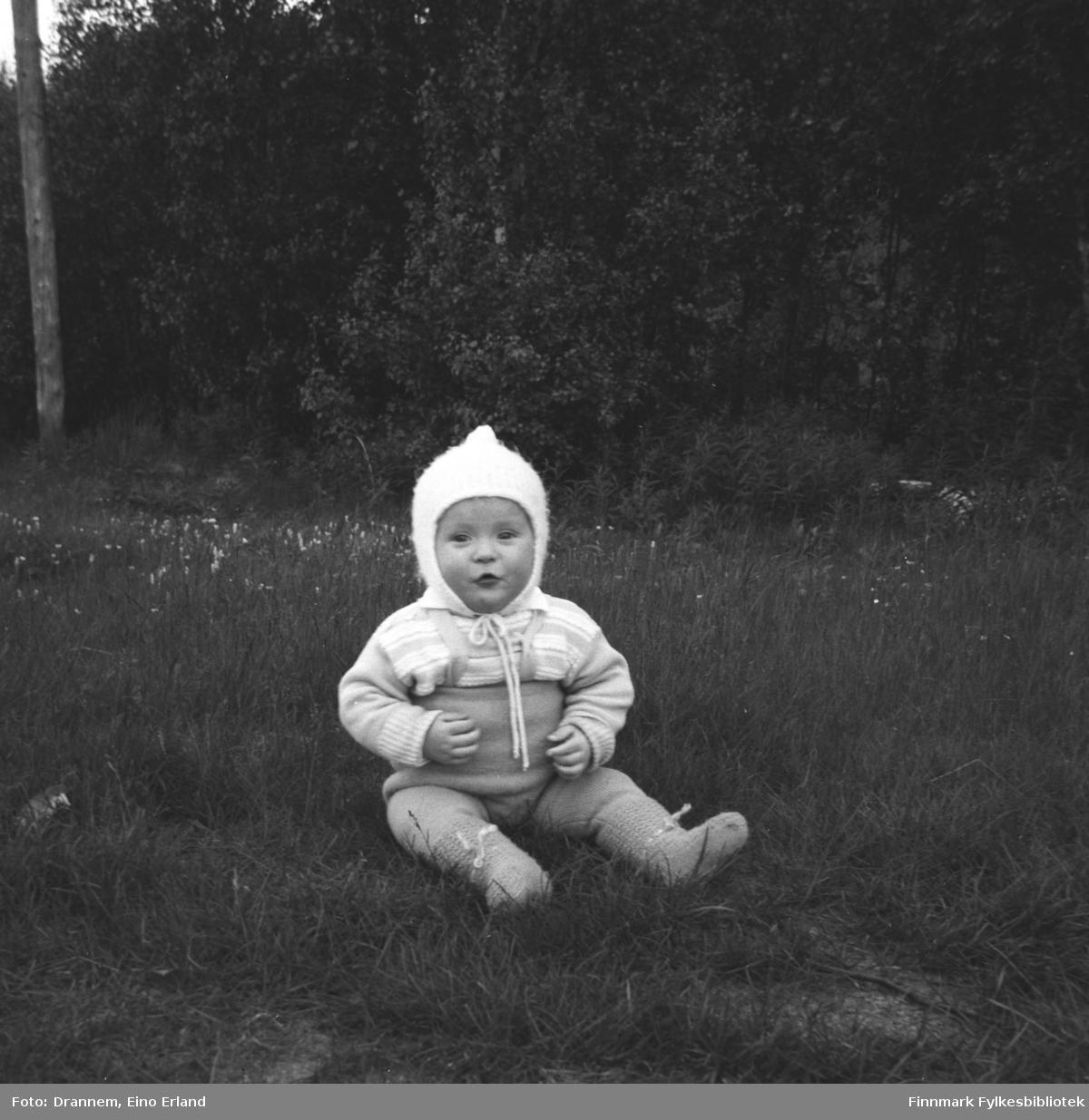 Bilde av et litet barn, antakelig Karl Magne Arvola, som sitter i gresset. Bildet er tatt sannsynligvis i Neiden.