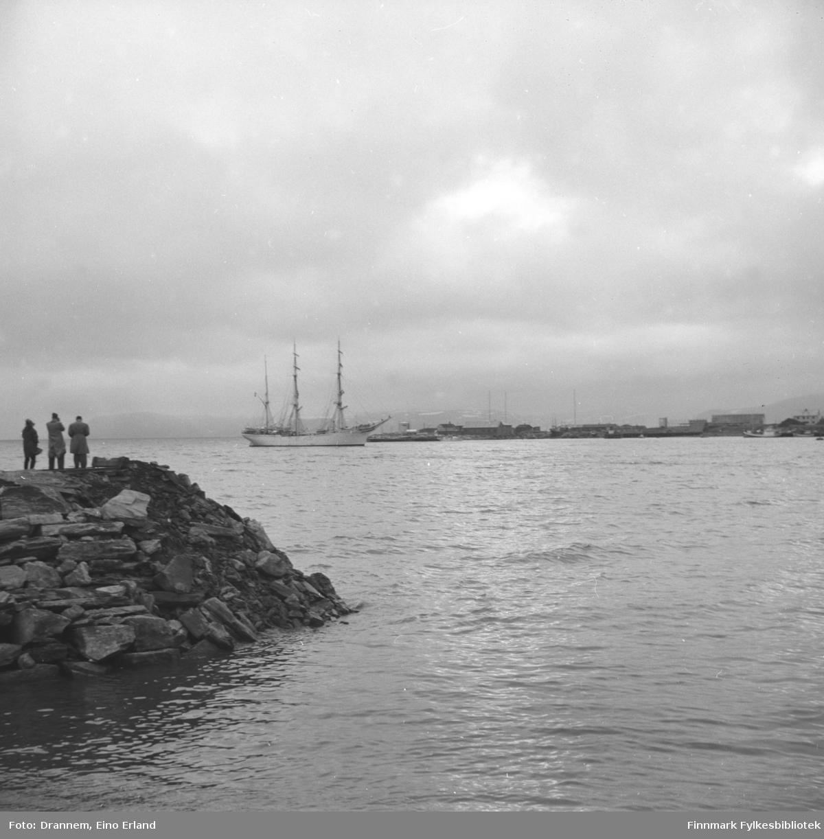 Utsikt mot Hammerfest havna. På venstre side av bildet ser man tre mennesker ståendes på moloen der de fotograferer og ser på skipet (med tre master og i hvit farge)