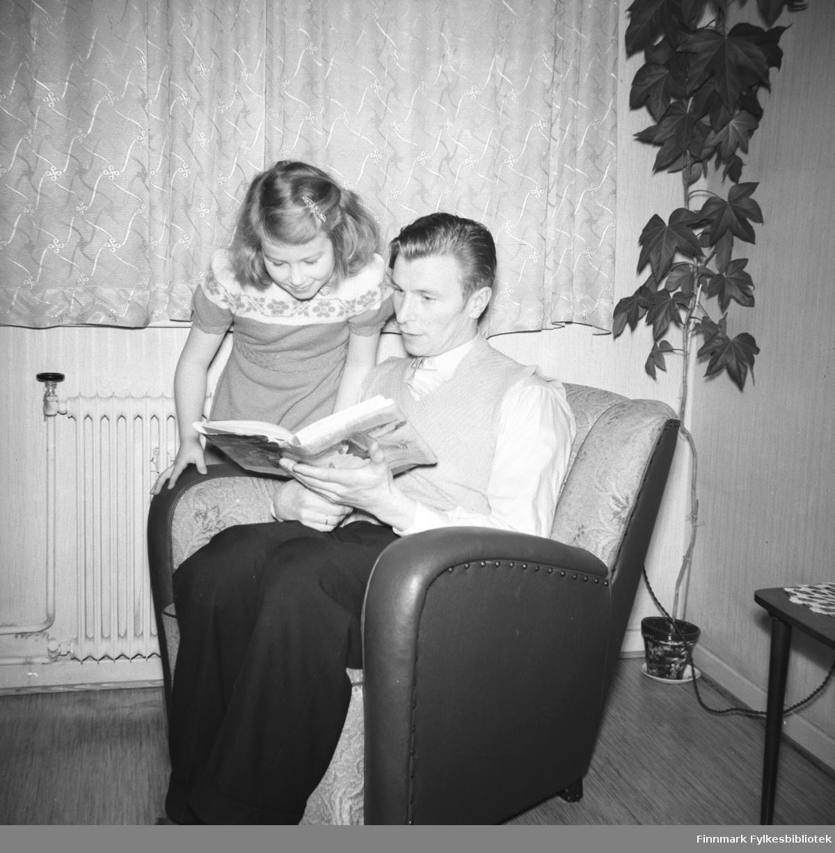 Eino Drannem med sin datter Turid Lillian sitter i lenestolen og leser ei bok