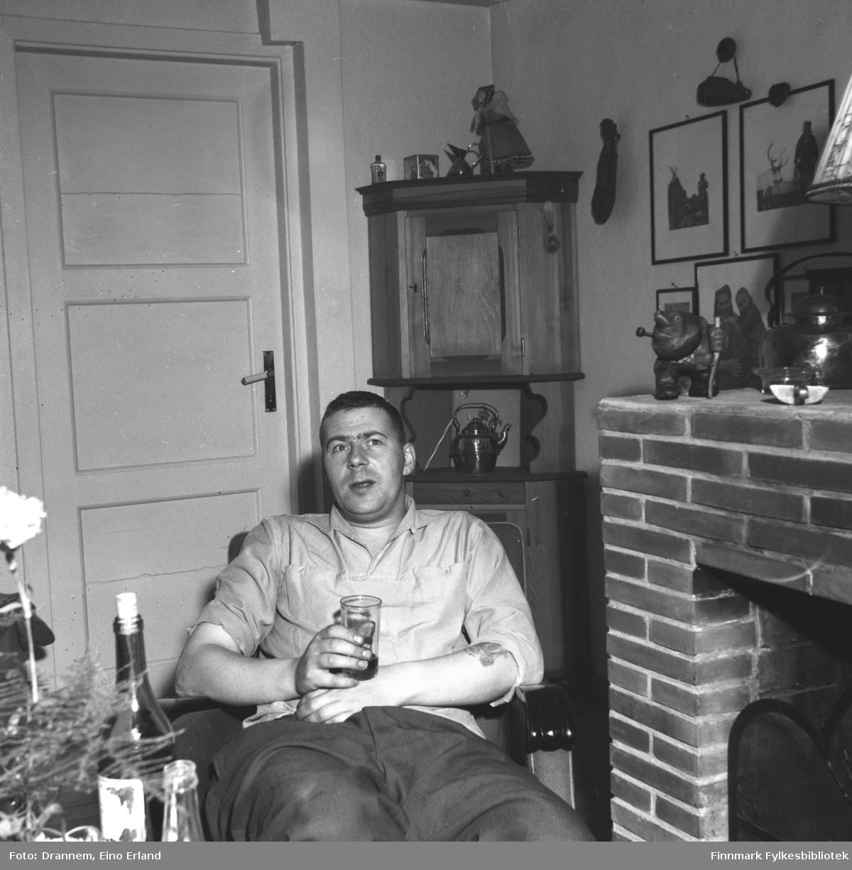En mann sitter i en lenestol glass i hånden