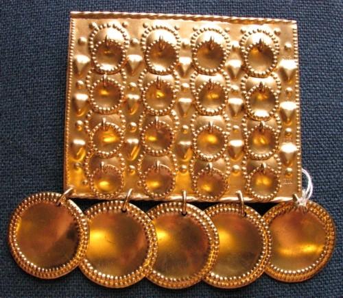 """Rektangulär silverplatta med 16 mindre hängen, """"löv"""", 9 mm i diameter, jämnt satta i 4 x4 rader med 4 löv i varje rad. I nederkanten hänger fem runda, större hängen, """"löv"""", 3,4 cm i diameter. Två upphängningsöglor på baksidan. Förgyllt silver."""