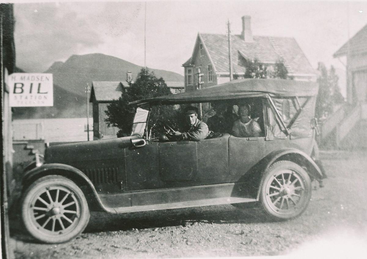 H. Madsen Bil Station, Sortland. Bilen er en Nash ca. 1923/24-modell. Bilstasjonen lå mellom Johnsengården og Arntzengården, det var den første drosjesentralen på Sortland. Ingvald Madsen ved rattet. Det var en kald fornøyelse å site på en 7 seter cabriolet.