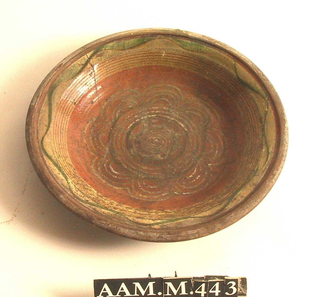 8-bladet rosett i gult og grønt mot rødbrun bunnfarge.