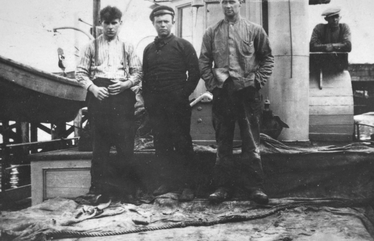 Fire menn fotografert på dekket til en båt. Båt, sted og personer er ukjent, men bildet kan være tatt i Kvalsund kommune før evakueringa.