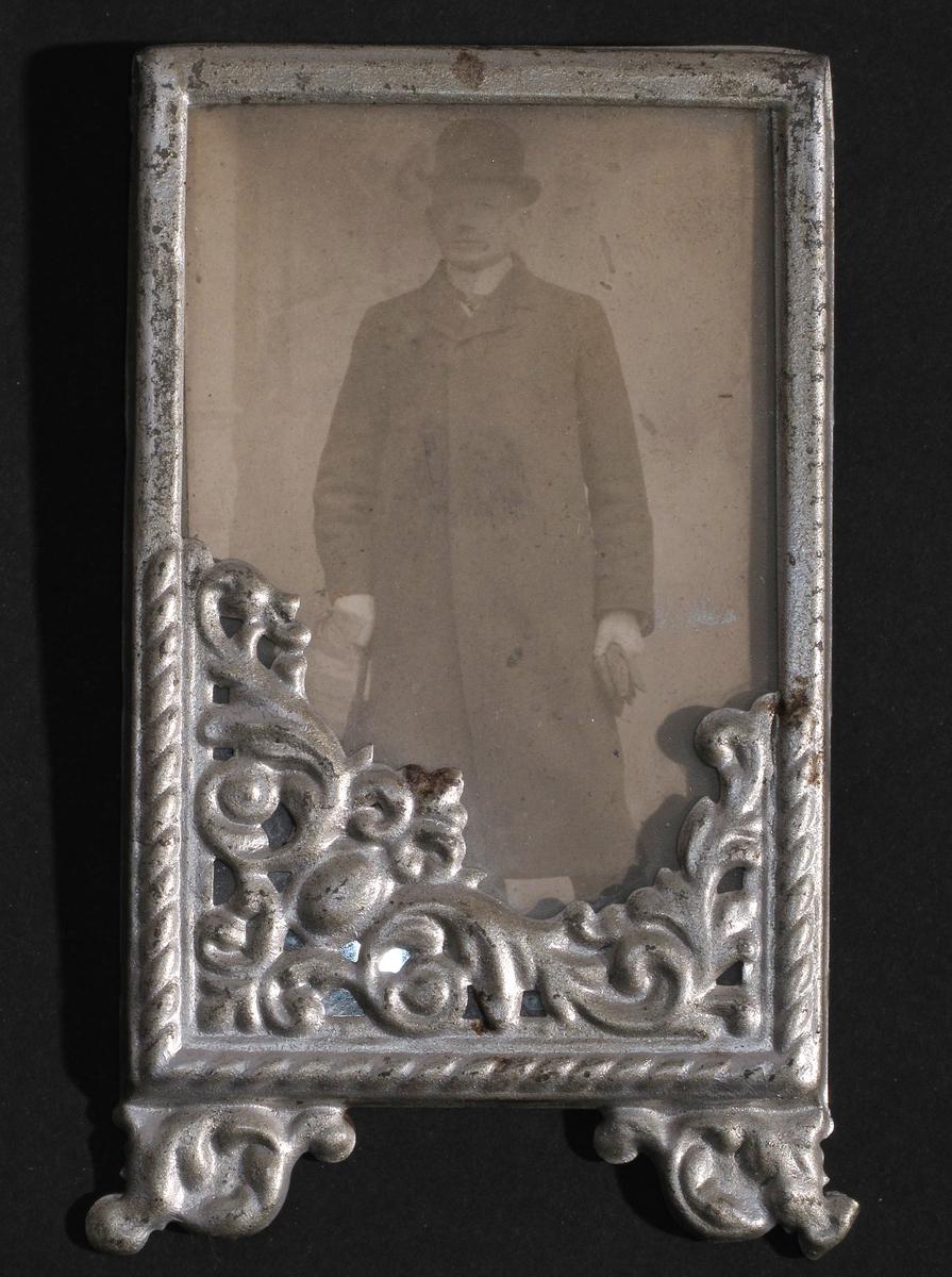 Portrett av ung sjømann  (?),  stående ung mann i helfigur,  en face, med knappet frakk og bowlerhatt,  paraply i den ene hånd, hansker i den andre, stiv snipp, lys bakgrunn med en søyle tv.  Rammens ornament fyller nedre, særlig v. hjørne.