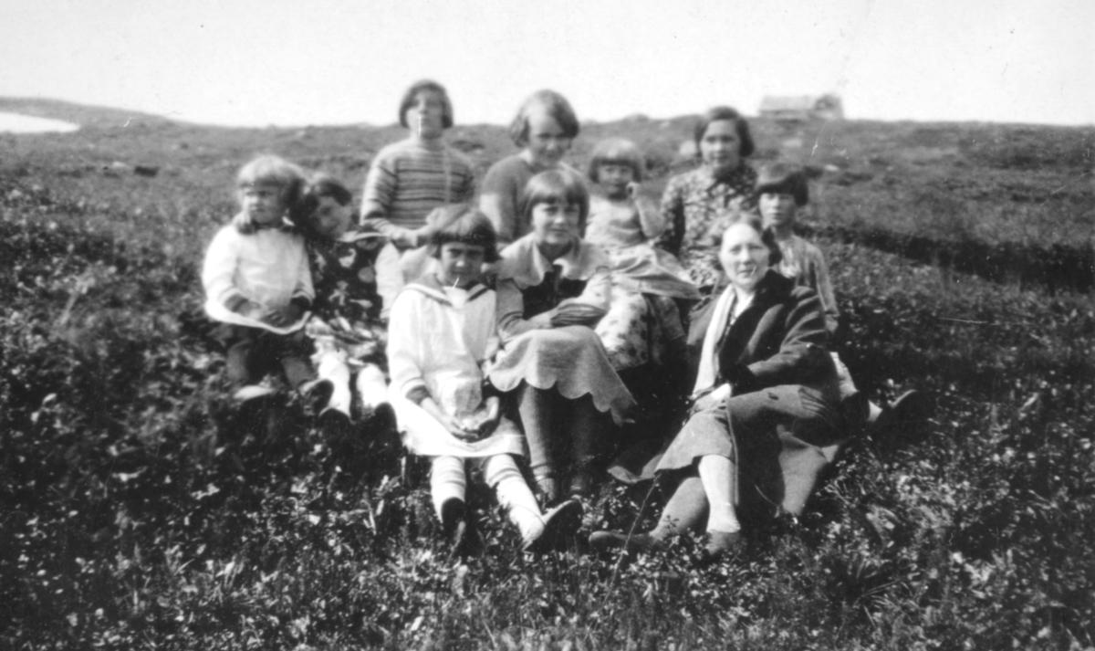 En kvinne med en liten flokk barn fotografert i terrenget, sansynligvis i Kvalsund kommune. Personene er ukjent.