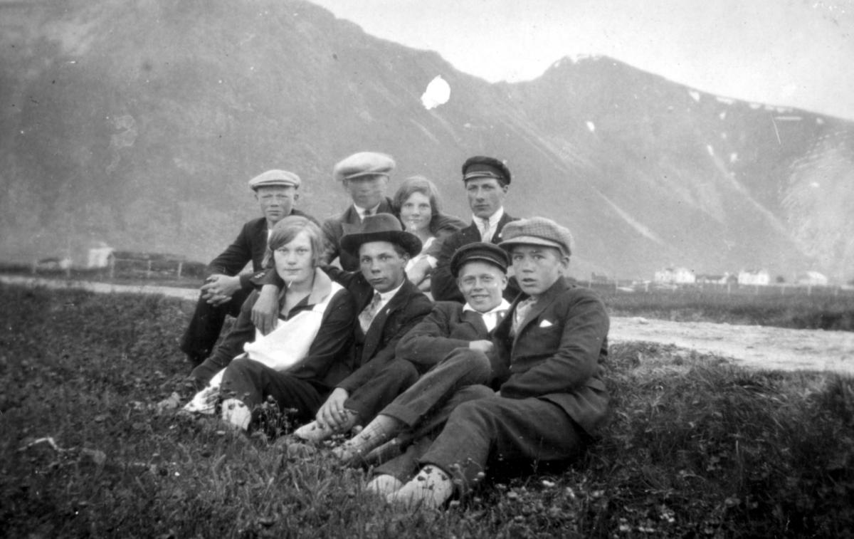 En gruppe pentkledte unge mennesker sitter i terrenget. Sted og personer er ukjent.