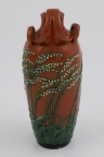 Kanne med hank i glasert leirgods. Konisk korpus, dekorert med liljekonvall i grønt og gult, fremstilt i lavt relieff på rødlig bunn. Lav hals, tut med nebb, samt to slyngende hanker med organisk utforming.