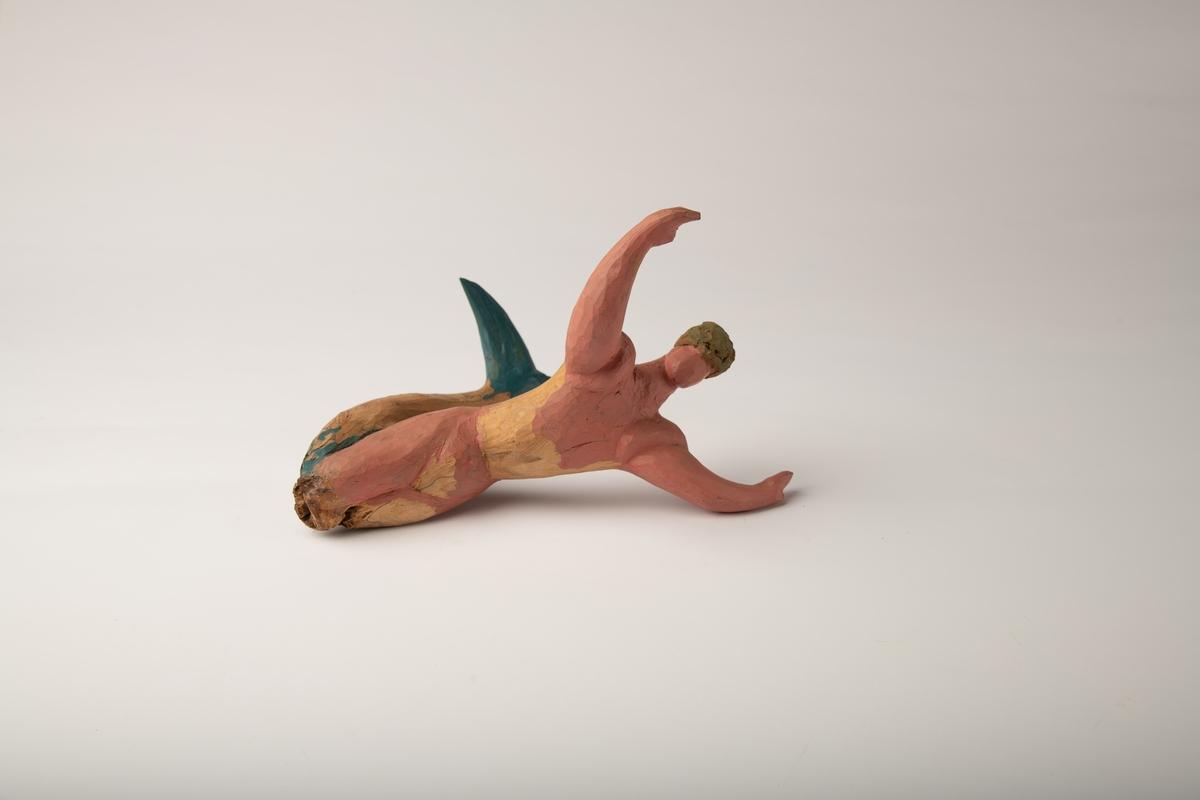 Mannsfigur i vinkel med blå halefinne og delvis rosa kropp. Hendene ut fra kroppen. Skåret av et stykke tre, der treets naturlige form har blitt en del av skulpturens form.