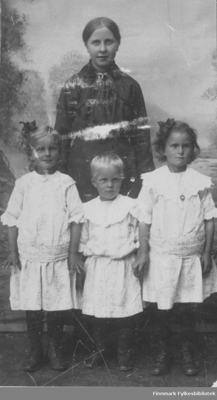 Mor kledd i svart kjole med tre jenter kledd i hvite kjoler.