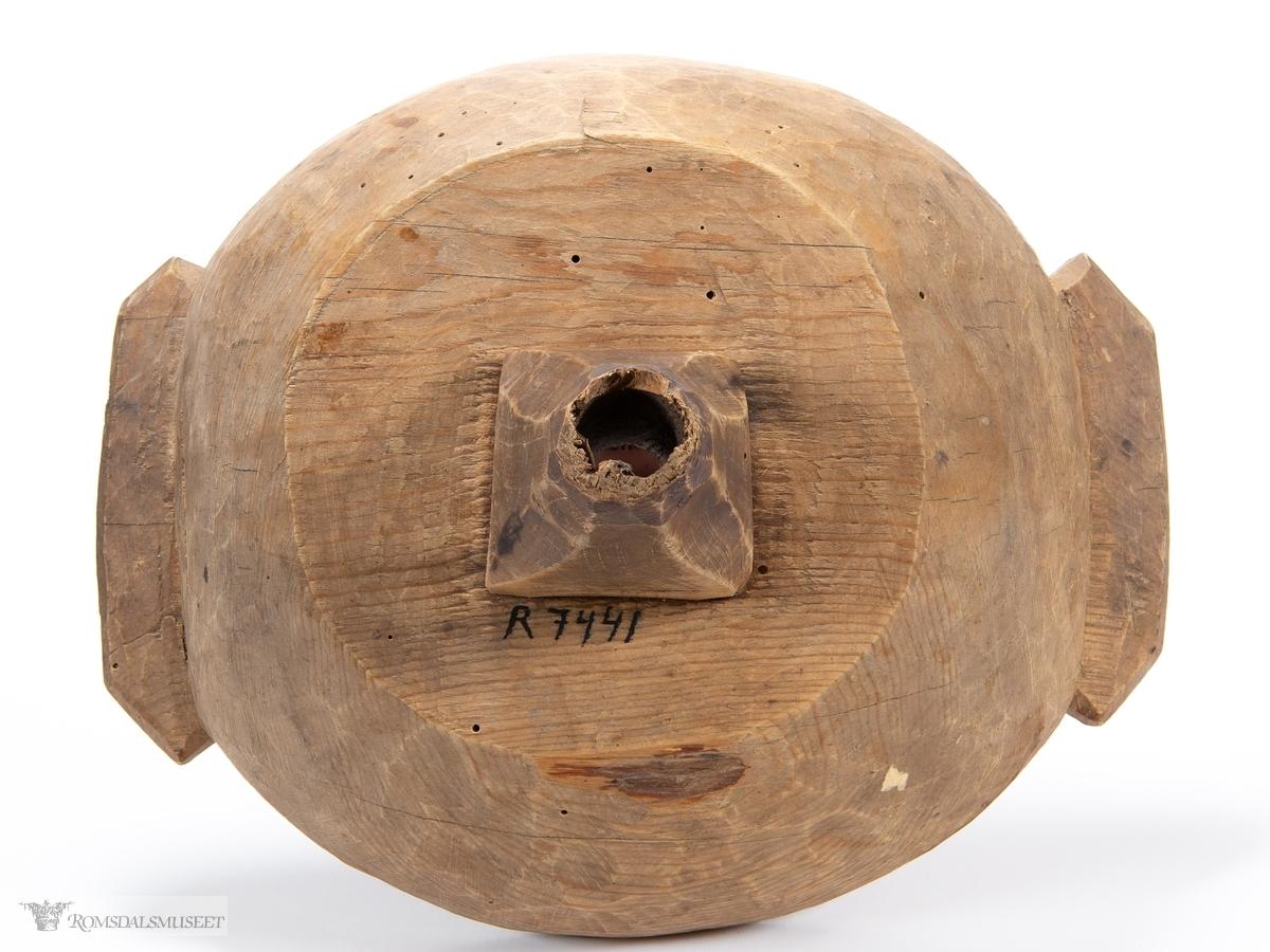 Uthulet trebolle med utskårne grep på hver side. Bunnen er flat og har en innfelt, skåret tut.