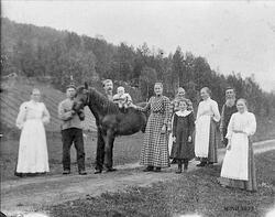 4 menn, 4 kvinner, ei jente, en mann setter et barn på heste