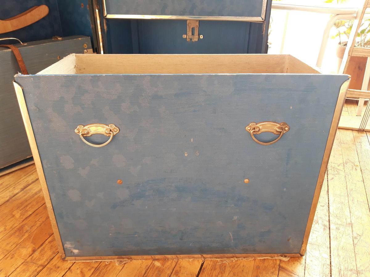 Stående koffert. Åpnes på den ene langsiden. Innsiden er tapetsert med blått plastbelagt lerret på den ene siden og blått lerretsstoff på den andre siden. Tre skuffer på den ene siden som kan tas helt ut. En metallstang er festet bak skuffene som når den vris låser skuffene fast. I den andre delen av kofferten er det øverst et metallstativ med 9 kleshengere i kryssfiner med ulikt design. Topplokket kan åpnes og metallstativet trekkes ut. På innsiden av topplokket er det en pute som sannsynligvis er ment å holder kleshengerne på plass når lokket er lukket. Midt på denne siden er det også en trestang som er festet i et metallbeslag på hver side. Denne er justerbar. En liten koffert i tre trukket i blått lerretsstoff er festet med en lærrem nederst på samme side.   Skroget er trefiberplate, som utvendig er malt i en grønn/brun farge.  Slitt overfflate. Kofferten er kantet med bånd malt i en mørkegrønn farge. Pynt og hjørnebeslag i metall. Lærhåndtak på  toppen.  Flere påklistrede reiseetiketter.   Adresselapp festet til lærhåndtaket på toppen med taksten: Utskiftingsformann Loe, Harstad. Adresselapp festet til lærhåndtaket på toppen fra Canadian Pacific Steamships