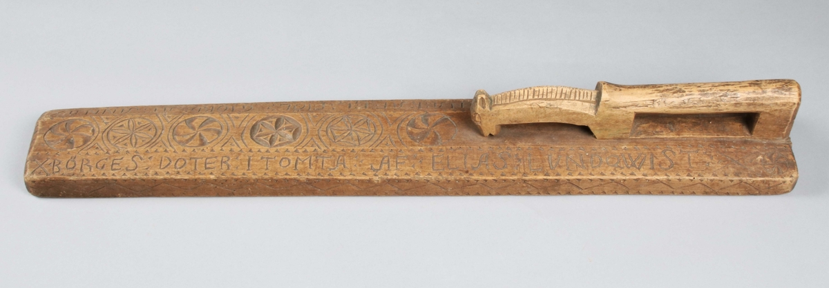 """Mangelbräde i brunbetsad lönn. Kraftigt bräde med nedfasade långsidor. Längs mitten av brädet, skuren dekor i form av fem bladrosetter och virvelhjul. På ena änden infällt handtag i form av häst. Längs kanten på båda sidor vågbård inom uddbårder. På de nedfasade långsidorna skuren text: """"ANNO 1769 ÄR DENNA KAFEL FIÖL GIORD ÅT ANNA BÖRGES DOTER I TOMTA AF ELIAS LUNDQWIST"""".  Mangelbräde eller kavelbräde är ett redskap av trä som använts för mangling av textilier. Mangelbrädet användes tillsammans med en kavel, en slät rulle av trä. Den textil, som skulle manglas, lades på ett bord eller annat slätt underlag. Under hårt tryck rullades kaveln med hjälp av mangelbrädet fram och tillbaka över tyget. (Wikipedia)"""