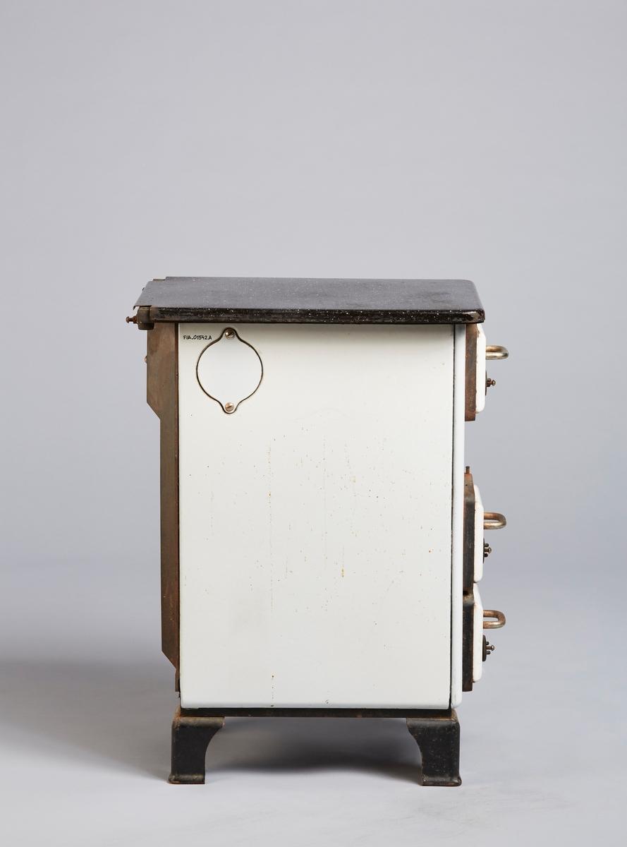 Komfyr tilhengeren er i emaljert jern. Den har en sort plate i jern øverst, der det kan stå gryter og panner. Den har sorte bein i jern. Ellers er den i hvit-emaljert jern. Den har tre innføringslemmer på fronten ned håndtak i galvanisert stål. Den øverste er til å putte inn ved og koks. Den mitrerste har en tremmelem og kan brukes til å regulere trekket i ovnen. Den nederste lemmen fører inn til askeskuffen, som er løs og kan tas ut. På siden av ovnen finnes et rørhul som kan brukes til å koble komfyrtilhengeren til et røykuttrekk.