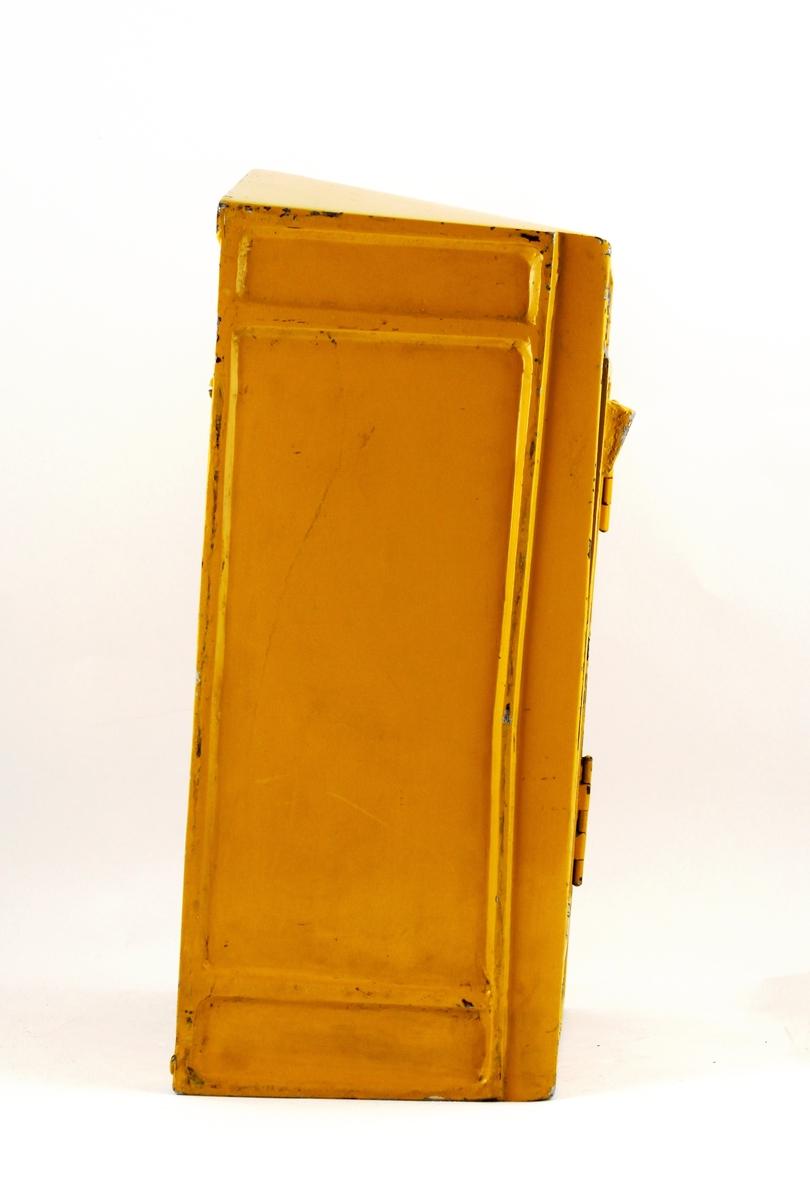 Brevlåda i gul järnplåt med arabisk och fransk text- Tömningslucka framtill med från insidan omställbara tömningstider. Brevinläggsöppning utan fällbar lucka, låst med från insidan nedfällbar klaff. Den arabiska texten ovanför iläggsluckan flankeras av femuddiga stjärnor.