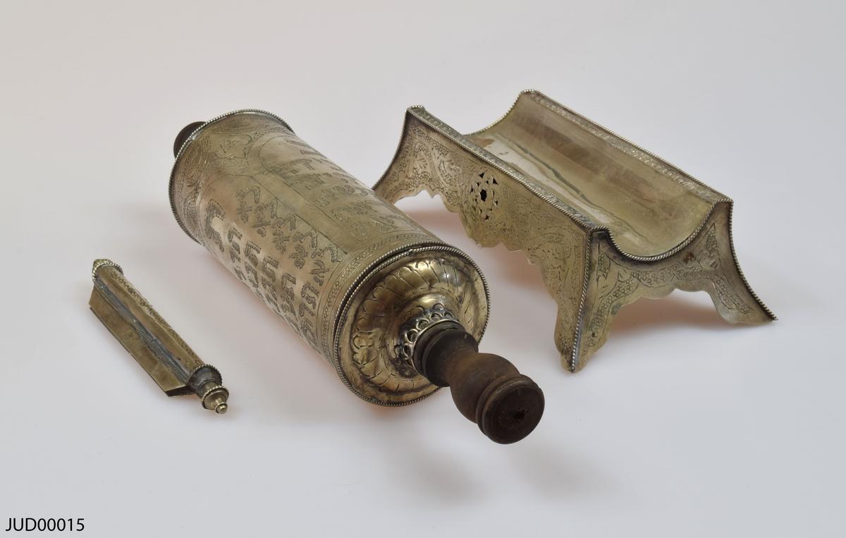 En tom silverrulle med trähandtag för Megillat Ester, med tilllhörande  stöd för rulle samt fäste för texten som båda är tillverkade av silver. Rikt dekorerad i form av gravyr, föreställande bland annat de tio budorden på hebreiska.