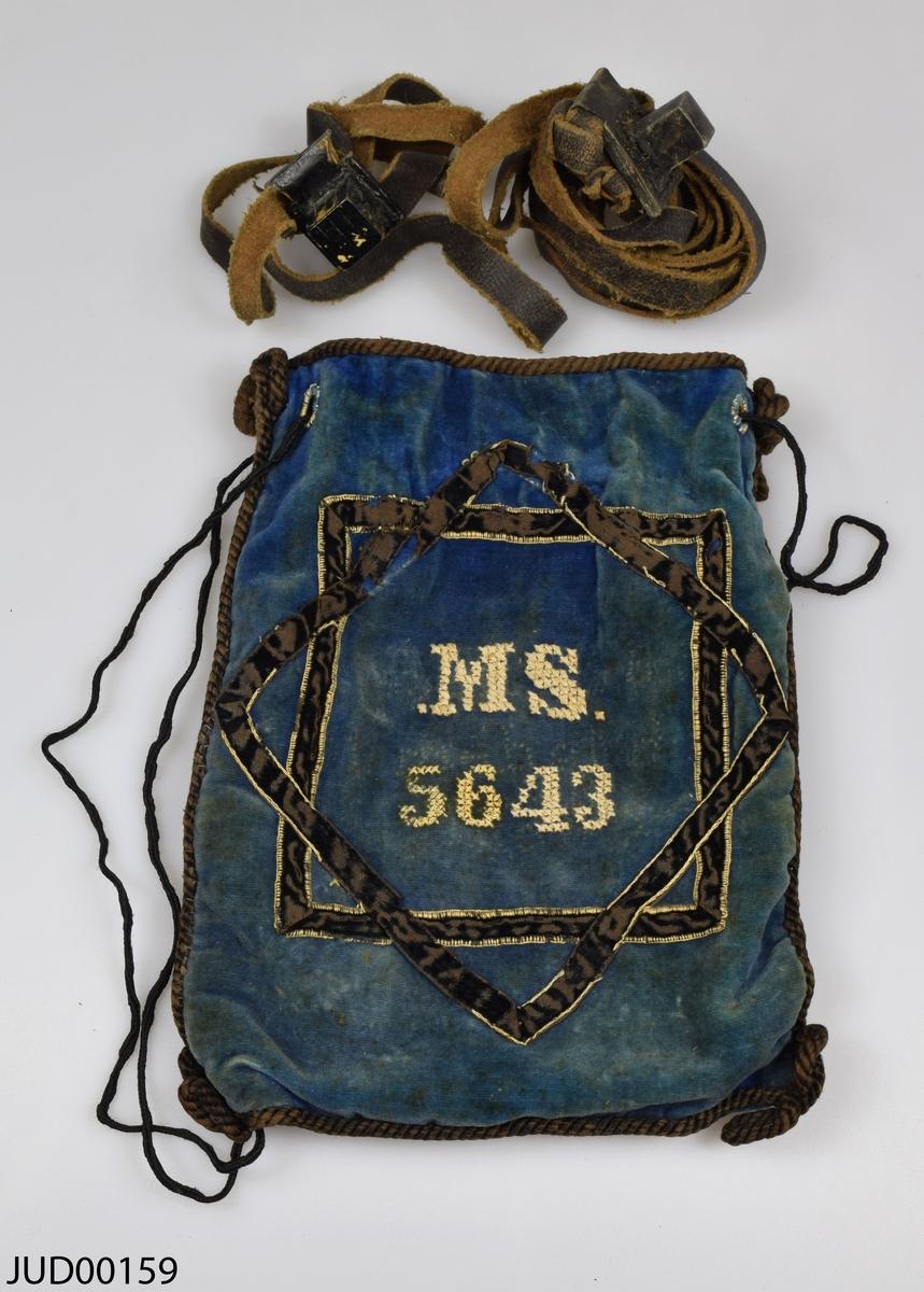 """Tefillinpåse tillverkad av blå sammet, med ett par tefillin liggandes i. Fastsydda snören i kanterna och i öppningen. Påsen är dekorerad med ett fastsytt svart sammetsband i form av en davidsstjärna, korsstygn i form av MS. 5643 [1882]. På andra sidan är en tysk text pärlbroderad: """"Fürchte Gott und halte seine Gebote demites Dir Wohl gehe""""."""