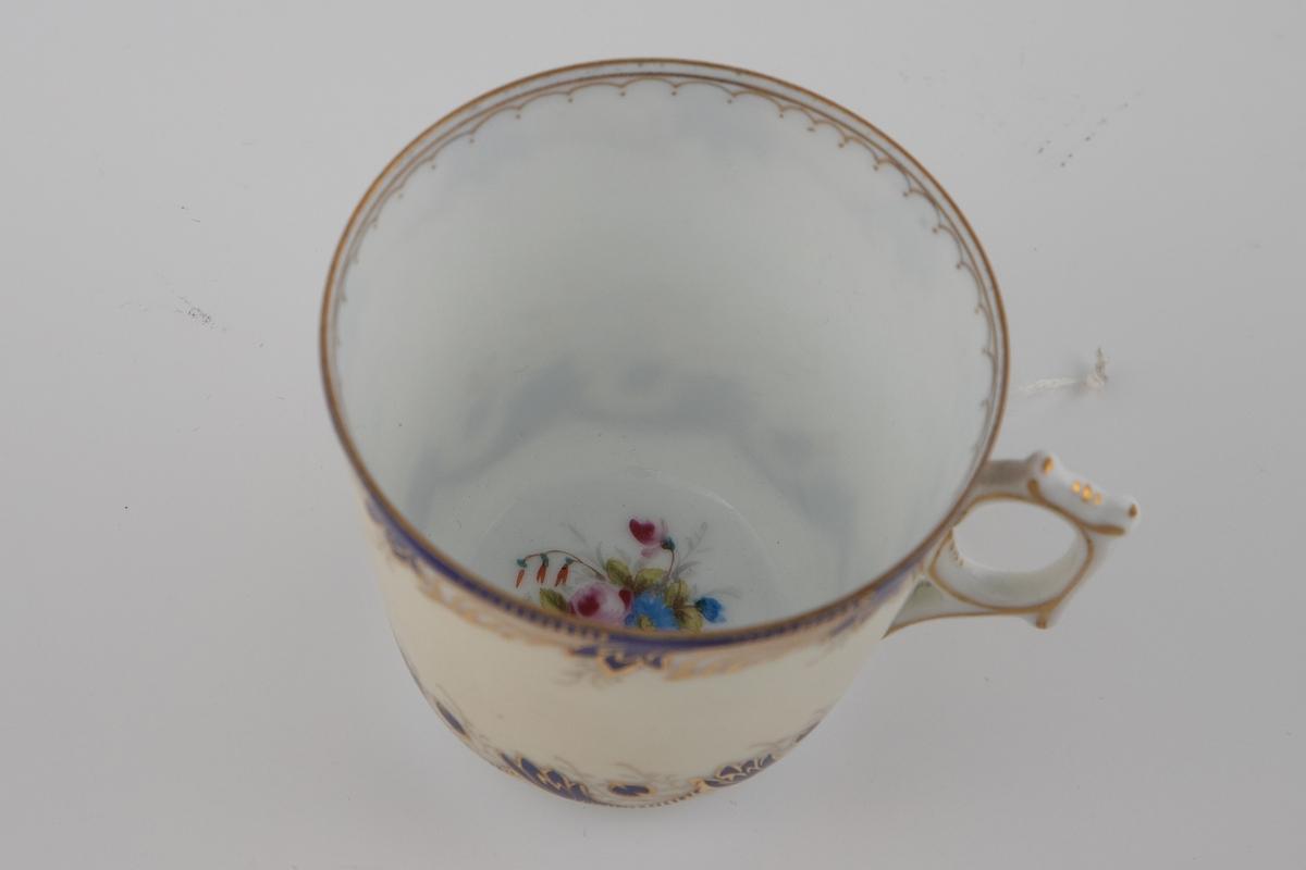 Kaffekopp med tilhørende skål i glasert porselen med overglasurmaling og forgylling. Koppens ytterside er kremfarget, og dekorert med en stilisert organisk bord i blått og gull på øvre og nedre del. Innsiden er hvitfarget med en enkel geometrisk bord nedenfor munningsranden. Skålen gjenopptar koppens motiver og fargepalett, med blå og forgylt detaljering på kremfarget bunn, samt et utsprat midtparti med rosa- og blåfargede blomster.