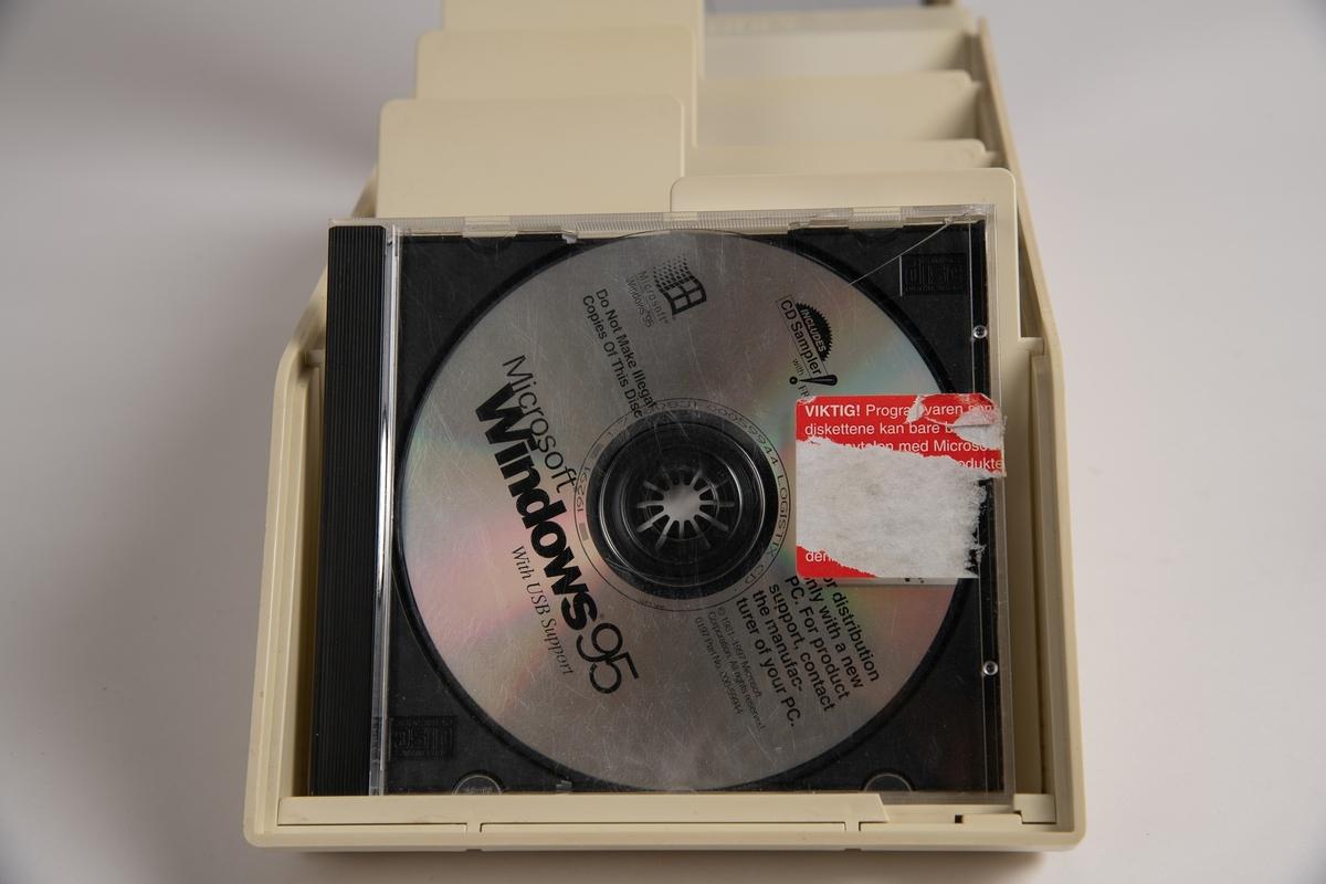 Hvit boks med gjennomsiktig lokk. Inneholder 11 CD-er. CD-ene inneholder ulike programvarer.  Er også to etuier til CD-plater.