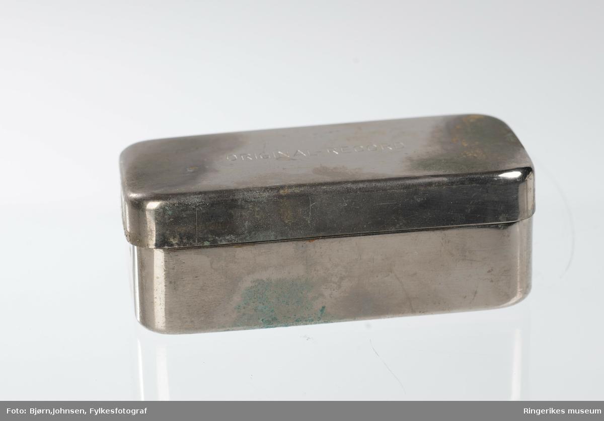 """10ml sprøyte og kanyle i metalletui og pappetui med metallbeslag i hjørnene. I pappesken er bruksanvisning med overskriften THYMOPHYSIN """"svak""""."""