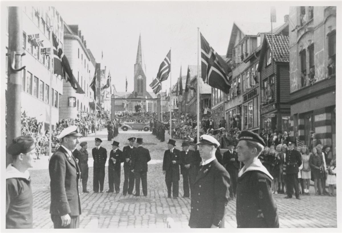 Alle venter spent på Kong Haakon VII som skal komme på besøk til Haugesund 22. august 1945. Oppe i Torgbakken står det en bil og venter som Kongen skal fraktes rundt i. Menn fra Hjemmefrontstyrkene er klare oppe i bakken og nede på kaien venter menn fra bystyret, ordfører og politimester. Noen marinegaster og marine-offiserer står i front. Oppover gaten ser vi folkemengder langs traseen som venter på å få et glimt av kong Haakon.