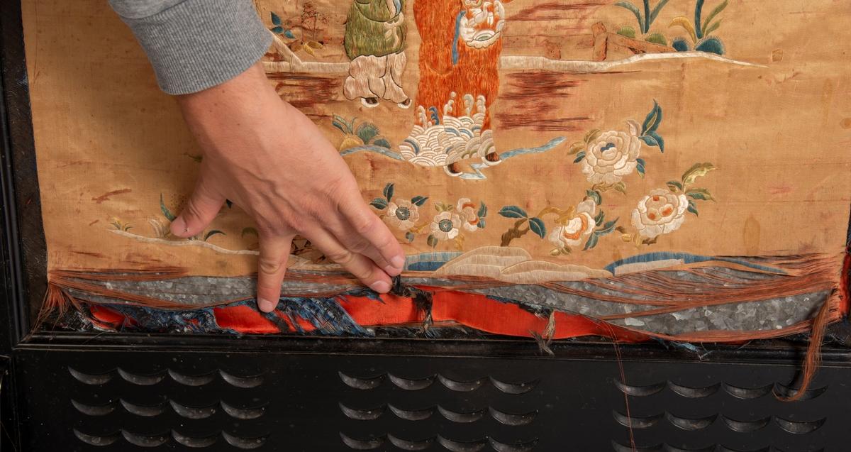 Svartlakkert ramme på 4 bein. Utskjæring av 6 blomstermotiv på toppstykket og 3 felt a 12 utskjærte bølger på nedre rammedel. Midtfeltet består av metallplate trukket med glanset bomull på baksiden og silkestoff med brodert asiatisk motiv på framsida.  2,5 cm bredt mønstret bånd limt på silkestoffet på alle 4 kanter., båndet består av en blanding av ull og silketråder.