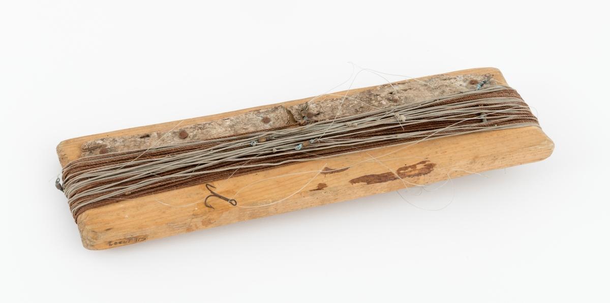 Snørevinne laget av et avlangt stykke tre. På vinna sitter to snører i bomull. Det er festet i alt 11 svivler med en viss avstand på snørene, og i hver av disse er det knyttet ei sene av nylon. I enden av fire av nylonsenene sitter en treblekrok. Sannsynligvis har det vært flere kroker enn dette. Det er spikret fast to avlange stykker bjørkenever på den ene siden av vinna, trolig for å ha noe å feste krokene i under oppbevaring.
