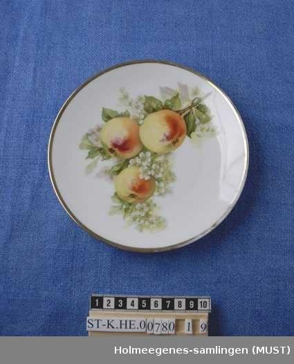 Fruktmotiver med gullstaffasje langs randen.