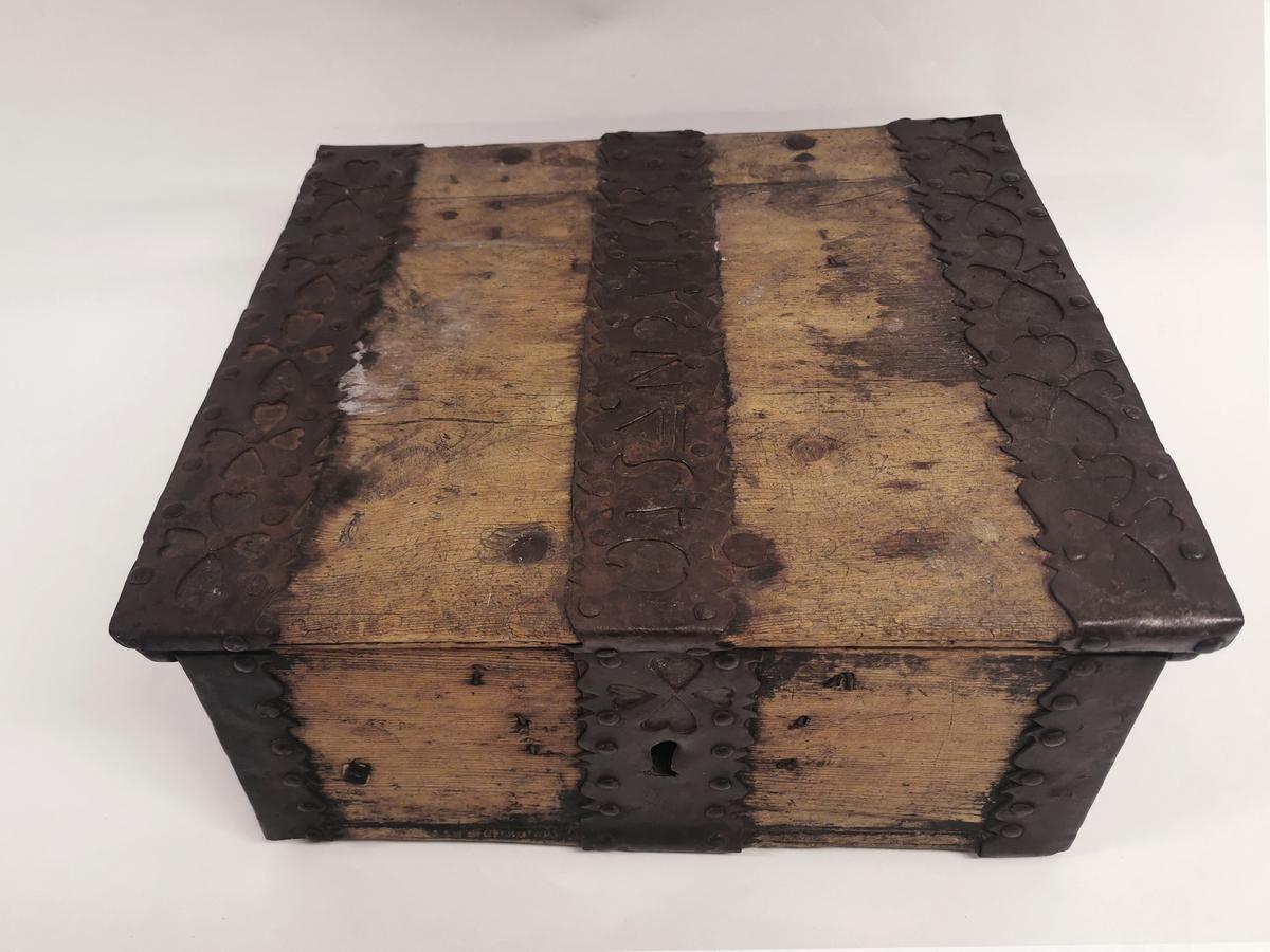 Ferdaskrin av tre med metallbeslag. Delene er spikret sammen. Bunnen består av to planker. Trapesformete sidevegger.