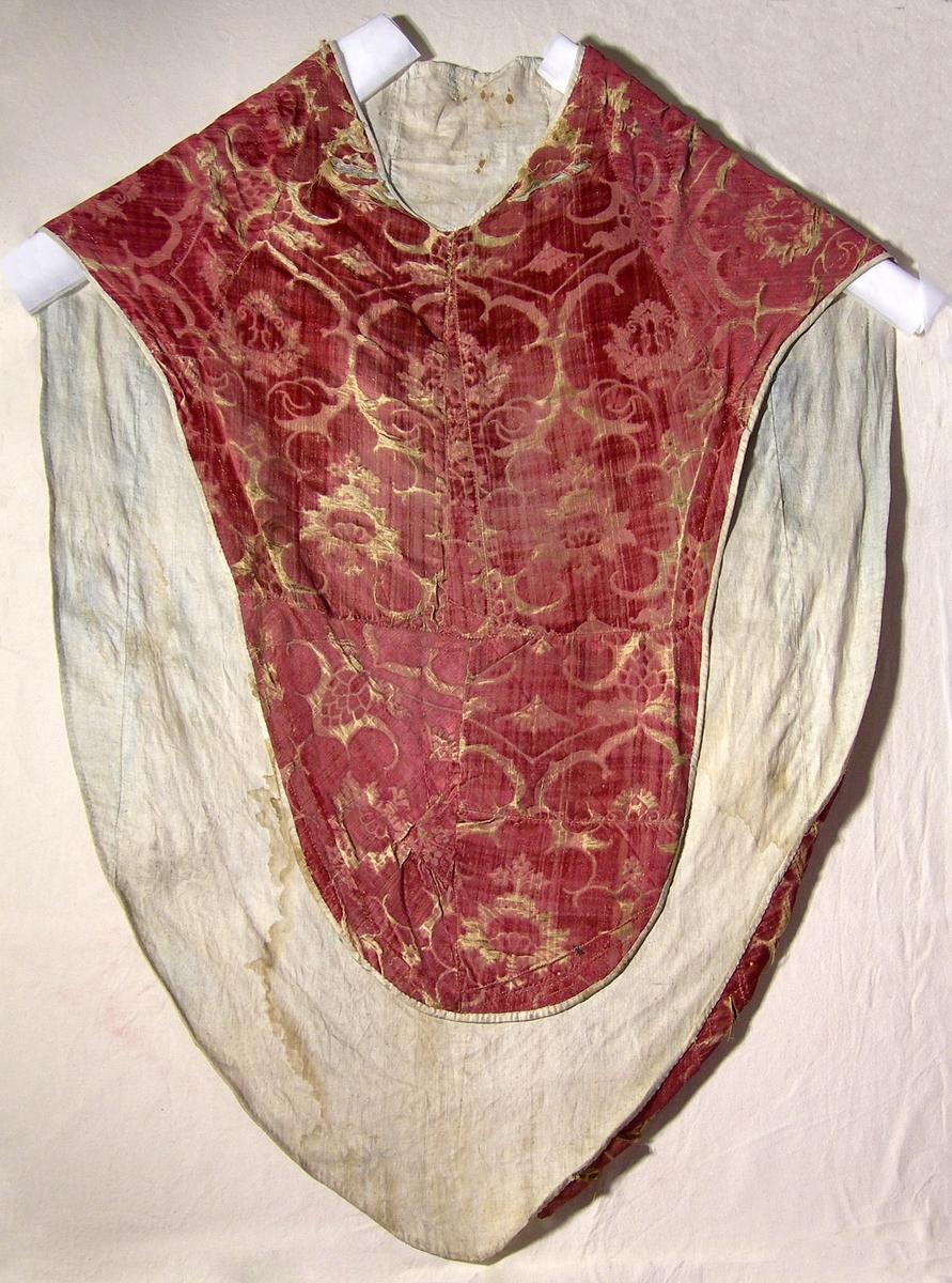 Mönstervävd sammet, röd. Varp: rött silke Polvarp: rött silke Inslag: gulvitt silke Stort granatäppelmönster, mönsterrapport 420 x 400 mm. Botten och detaljer i 5-skaftad satin, mönster i skuren sammet. Linnefoder, tuskaft, oblekt. Fodret vikt runt ytterkanten och fastsytt mot sammetstyget. Mässhaken saknar axelsöm och är sydd av flera delar. Sömmar i lintråd. En ca 150 mm bred remsa saknas mitt i ryggpartiet; tråd- och stygnrester i linnefodret, en del lätt blåtonade.
