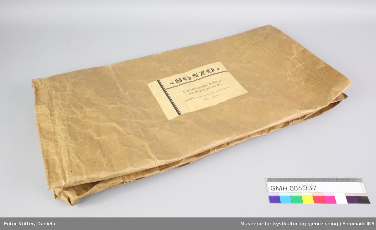 Papirposen er laget av brun papir og har en åpning på langside. Den har påført en etikett og har kostet 1,40 kroner.