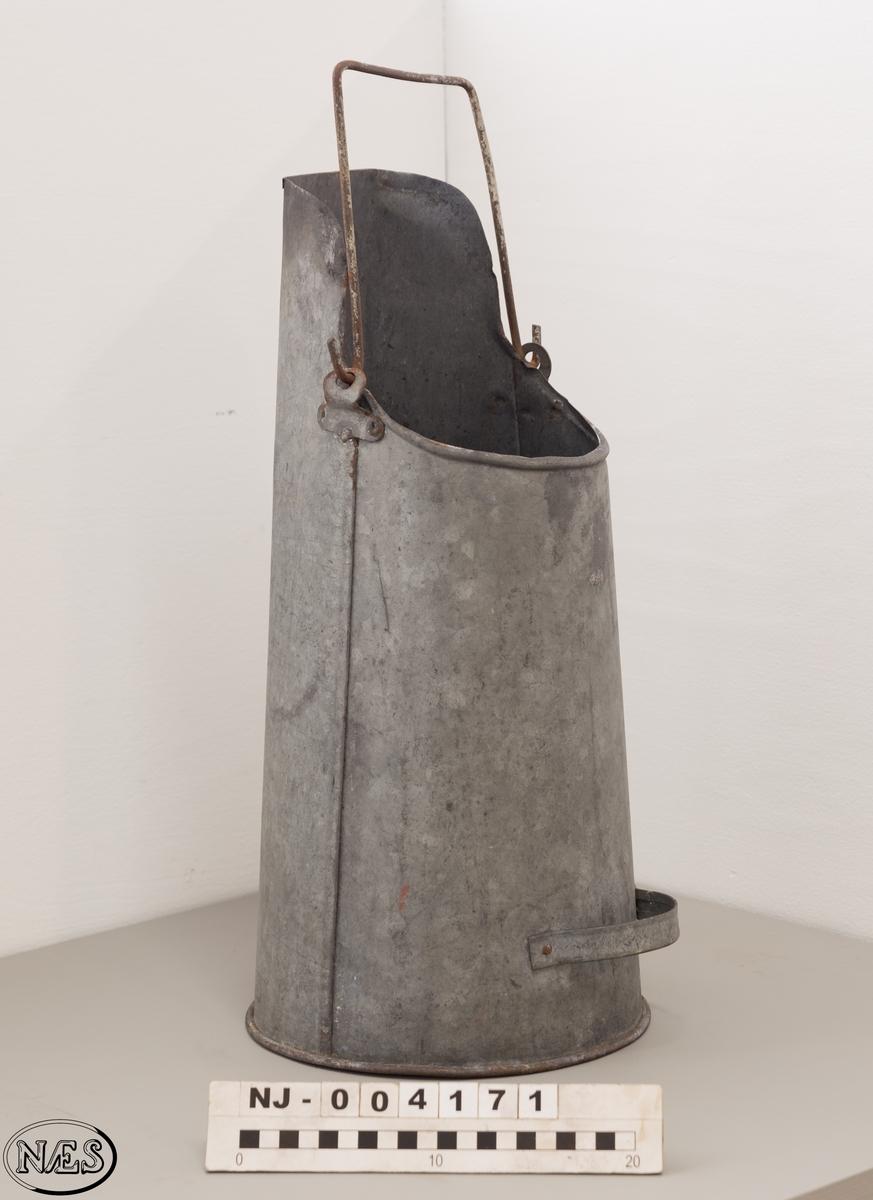 Sylinderformet koksbeholder med håntak. Smalner av mot toppen.