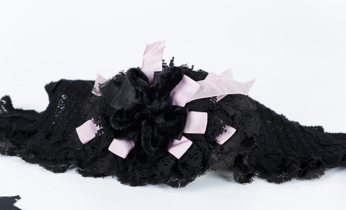 Hodekappe. Avlanng kantet bunn i sort maskinlaget stoff med åpen strikkestruktur kantet med maskinlaget knipling. Midt foran rosett av rosa og sort silkebånd og fløyelsnor. Knyttes under haken med sorte silkebånd. Tilstand god.  Antakelig brukt av Amalie eller Anette Gaavim.