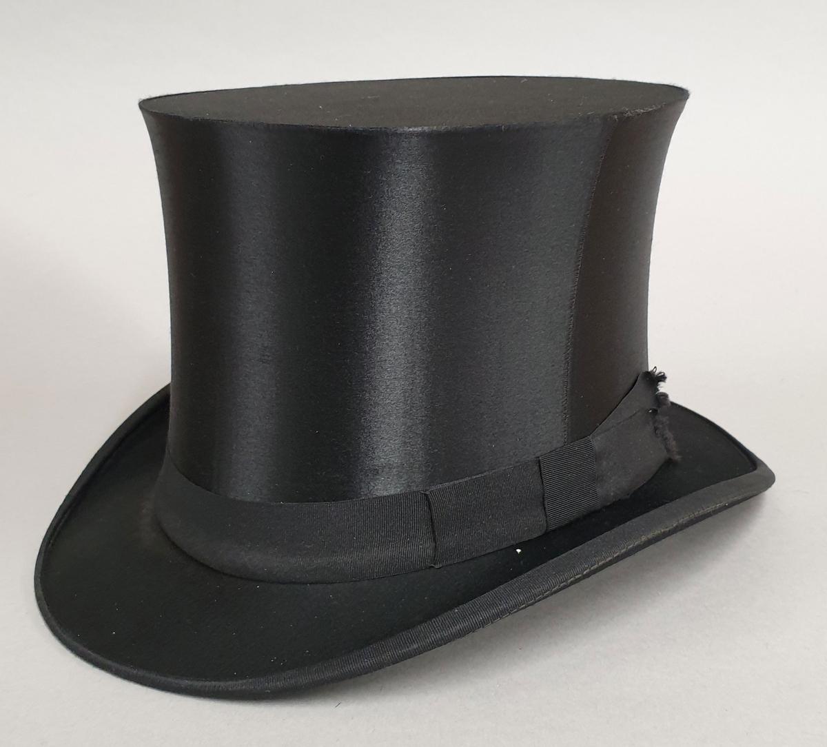 Flosshatt med silketrekk og ripsbånd rundt pullen. Fôret med stripete silke i grått og sort, og med produsentens signatur.
