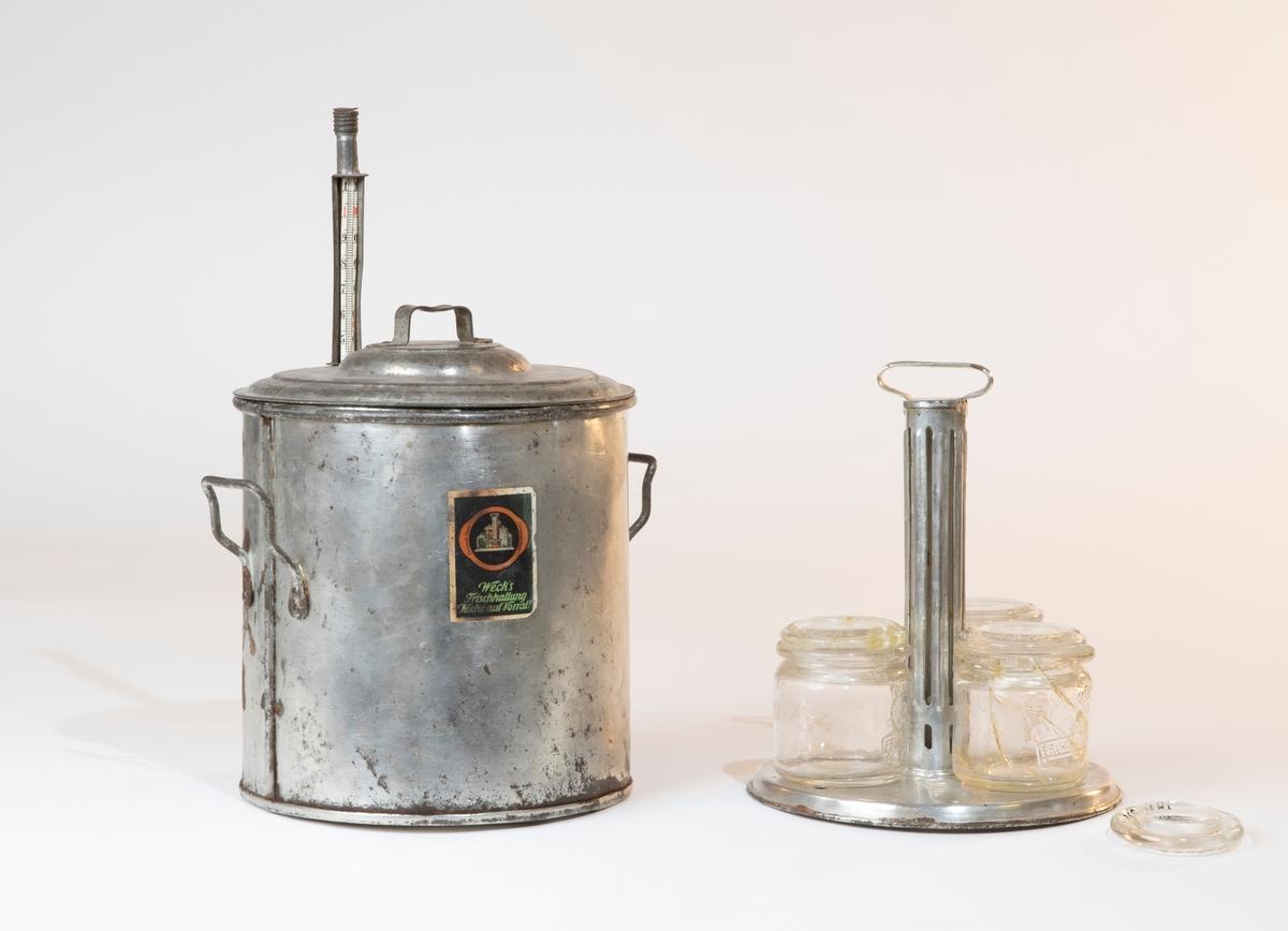 """Konserveringsapparat, leksaksapparat. Lock till konserveringsapparat med ett hål i (för termometern). Nitat handtag överst. Samhör med konserveringsapparat JM.24632:1a-d.  Konserveringsapparat av plåt JM 24632:1-5. I locket ett hål med plats för en termometer med temperaturgradering av papper. Inuti apparaten en ställning med plats för konserveringsburkarna. Ställningen består av en  botten som är perforerad för att vattnet ska rinna av. Från botten ett stativ, för stöd för burkarna, avslutad med ett handtag att lyfta i. Till apparaten hörde ursprungligen fyra stycken konserveringsburkar av glas med glaslock.   Konserveringsburkar av pressat glas med ett hjärta och texten: """"SHUTZ MARKE 3. W. FRISCHHALTUNG"""" på framsidan och """"WECK'S FRISCHHALTUNG"""" i botten. Glaslock till burkarna med texten: """"WECK'S FRISCHHALTUNG 65E""""."""
