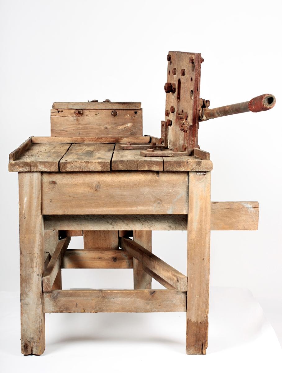 Bordkonstruksjon av spikrede grove trematerialer. På en side påmontert kutteanordning i jern for å kutte flatjern i biter. På annen side påmontert anonrdning i jern for å bøye bitene.