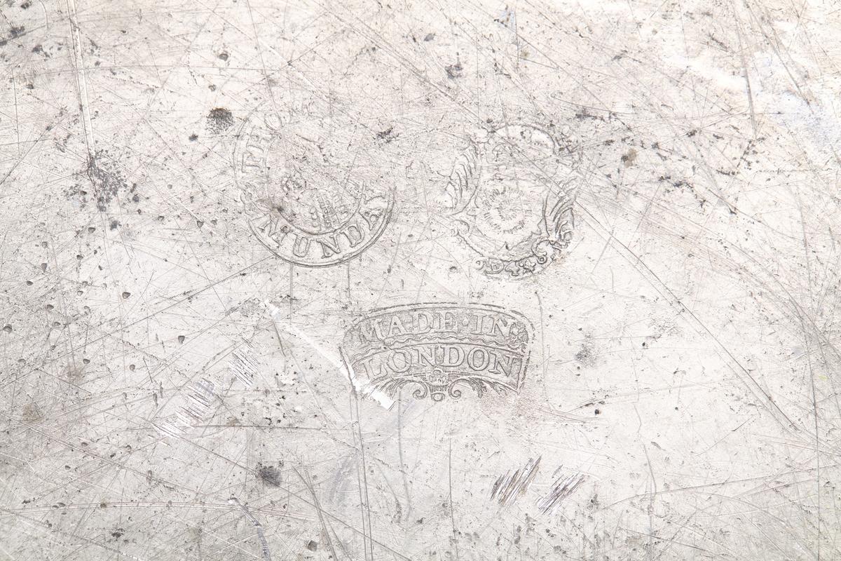Rundt tinnfat med flatt speil som runder jevnt opp mot kraven. Her er skarp overgang til kraven som skrår litt oppover med en fortykning under kanten. Tre store stempler; et mannsportrett med bokstavene Thomas Munday rundt, et våpenskjold med en krone over en rose og 694, og nedenfor Made in London. Fire små stempler; først T.M., deretter et mannsportrett med stor hårfylde, videre et løveansikt med store værhår og til sist et kvinnefigur som holder en lang stav i hånden over et våpenskjold.
